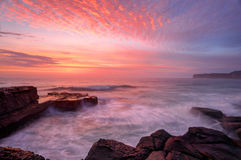 North Avoca sunrise seascape. Glorious summer sunrise skies over North Avoca rockshelf and a soft sea spray mist and motion in the waves.  NSW Australia Royalty Free Stock Images