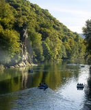 The North Caucasus mountain river close to the rock in the forest. Relaxing on a boat floating on a mountain river close to the rock in the forest Royalty Free Stock Photo