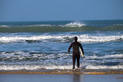 North Devon Surfer. The surfer faces his waves as he enters the water Royalty Free Stock Photography