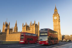 Big Ben and red buses. North face of Big Ben with houses of parliament, in London, UK, and motion blurred red double decker buses passing by stock photos