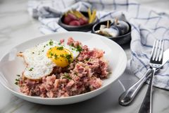 North German Hamburg Labskaus is a delicacy with corned beef, potatoes, beetroot, pickled gherkins, fried egg and herring on. Porcelain plate stock photo