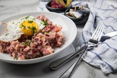 North German Hamburg Labskaus is a delicacy with corned beef, potatoes, beetroot, pickled gherkins, fried egg and herring on. Porcelain plate royalty free stock image