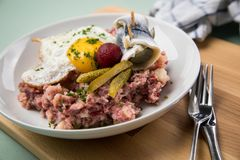North German Hamburg Labskaus is a delicacy with corned beef, potatoes, beetroot, pickled gherkins, fried egg and herring on. Porcelain plate royalty free stock photography