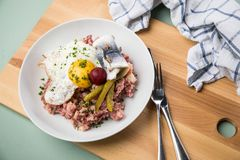 North German Hamburg Labskaus is a delicacy with corned beef, potatoes, beetroot, pickled gherkins, fried egg and herring on. Porcelain plate royalty free stock photos
