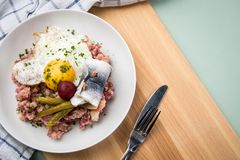 North German Hamburg Labskaus is a delicacy with corned beef, potatoes, beetroot, pickled gherkins, fried egg and herring on. Porcelain plate royalty free stock images