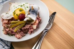 North German Hamburg Labskaus is a delicacy with corned beef, potatoes, beetroot, pickled gherkins, fried egg and herring on stock photos