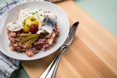 North German Hamburg Labskaus is a delicacy with corned beef, potatoes, beetroot, pickled gherkins, fried egg and herring on. Porcelain plate stock images