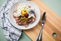 North German Hamburg Labskaus is a delicacy with corned beef, potatoes, beetroot, pickled gherkins, fried egg and herring on. Porcelain plate royalty free stock photo