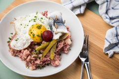 North German Hamburg Labskaus is a delicacy with corned beef, potatoes, beetroot, pickled gherkins, fried egg and herring on. Porcelain plate stock photos
