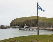 Island harbour and flag pole Royalty Free Stock Photos