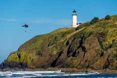 North Head Lighthouse. Coast guard helicopter in the sky. North Head Lighthouse at Pacific coast, Cape Disappointment, built in 1898, WA, USA. Coast guard Royalty Free Stock Image