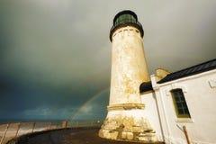 North Head Lighthouse and double rainbow. A double rainbow arches over the sea in the background of this view of North Head Lighthouse on the Washington Coast Stock Photos