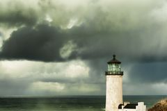North Head Lighthouse under stormy skies. Heavy clouds from stormy skies hang over the ocean while the ever present North Head Lighthouse stands in the Stock Image