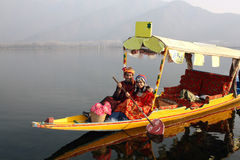 North Indian Couple riding Shikara Boat. Traditional North Indian couple in Pathani (Kashmir) dress riding a small yellow Shikara boat Royalty Free Stock Photos