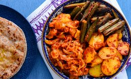 Indian vegetarian meal - North Indian main course. North Indian meal consisting of parantha and sindhi tawa sabji fried okra,potatoes and onions eaten for party Royalty Free Stock Image