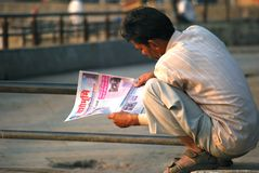 A north Indian migrant to Mumbai sitting in the streets of Mumbai early morning reading newspaper printed in his native language. Royalty Free Stock Photos