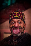 NORTH ISLAND, NEW ZEALAND- MAY 17, 2017: Close up of a Maori man sticking out tongue with traditionally tatooed face in. Traditional dress at Maori Culture Royalty Free Stock Photo