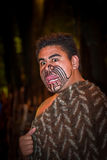 NORTH ISLAND, NEW ZEALAND- MAY 17, 2017: Close up of a Maori man sticking out tongue with traditionally tatooed face and. In traditional dress at Maori Culture Royalty Free Stock Photography