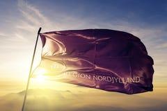 North Jutland Region of Denmark flag textile cloth fabric waving on the top sunrise mist fog. Beautiful stock photos