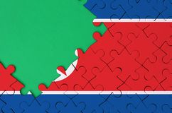 North Korea flag is depicted on a completed jigsaw puzzle with free green copy space on the left side.  royalty free stock images