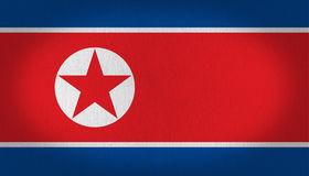 North Korea flag. With a white circle at the center left side and a red star in it with blue, red and withe stripes, fabric texture background vignette royalty free illustration