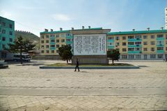 North Korea. Kaesong. Kaesong, North Korea - May 5, 2019: Typical view of the modern Kaesong city. Apartment buildings and square with local people rushing for royalty free stock photography