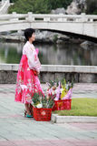 North korea 2013. North Koreas flower girl standing on the street in Pyongyang.Here is Pyongyang mansudae Park.She sold flowers to foreign visitors went to  Kim Stock Images
