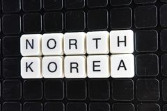 North Korea text word crossword. Alphabet letter blocks game texture background. White alphabetical letters on black Royalty Free Stock Image