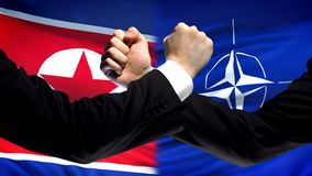 North Korea vs NATO confrontation, interests conflict, fists on flag background. Stock photo royalty free stock images