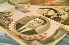 North Korean currency. Close up of an 100 Won note from North Korea, on a heap of North Korean notes of different values. The portrait shows Kim Il-Sung, who was Royalty Free Stock Images