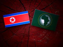 North Korean flag with African Union flag on a tree stump isolat Stock Photo