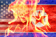 North korean flag fading into american flag with fire in front Royalty Free Stock Images