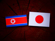 North Korean flag with Japanese flag on a tree stump isolated Royalty Free Stock Images