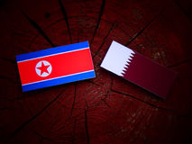 North Korean flag with Qatari flag on a tree stump isolated. North Korean flag with Qatari flag on a tree stump Stock Photography