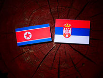 North Korean flag with Serbian flag on a tree stump isolated Royalty Free Stock Photos