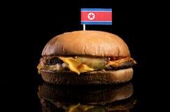 North Korean flag on top of hamburger on black. Background stock photography
