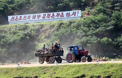 North korean village scenery. Here is the north korean village scenery on the way to Pyongyang.A tractor carrying farmers on the road in the countryside Stock Photography
