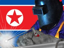 NORTH KOREAN WELDER WITH BACKGROUND OF HIS FLAG WAVES. WORKER THAT GENERATES WELL-BEING AND RICHES TO HIS COUNTRY stock photos