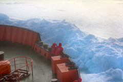 Icebreaker makes its way to North pole through pack ice. On bow of ship tourists, Ahead of rate is ice toros Stock Photography