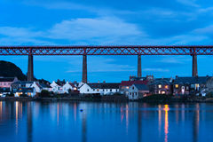 North Queensferry. Town of North Queensferry at blue hour, after sunset. Forth rail bridge connecting Edinburgh to Fife on background Royalty Free Stock Photos