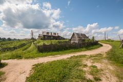 North Russian village Isady. Summer day, Emca river, old cottages on the shore, old wooden bridge. Abandoned building. Stock Photo