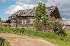 North Russian village Isady. Summer day, Emca river, old cottages on the shore, old wooden bridge. Abandoned building. Stock Photos