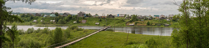 North Russian village Isady. Summer day, Emca river, old cottages on the shore, old wooden bridge and clouds reflections. stock image