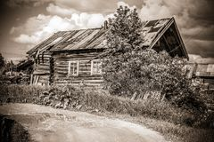 North Russian village Isady. Summer day, Emca river, old cottages on the shore, old wooden bridge. Abandoned building. Royalty Free Stock Photos