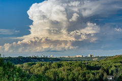 North Saskatchewan river Valley. Leading to downtown of the city of Edmonton with one predominant heavy cloud and blue sky background stock image