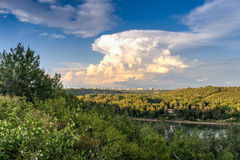 North Saskatchewan river Valley. Leading to downtown of the city of Edmonton with one predominant heavy cloud and blue sky background stock images