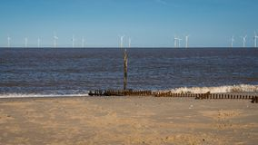 North sea coast in Caister-on-Sea, Norfolk, England, UK. With a wave breaker and wind turbines in the background royalty free stock photos