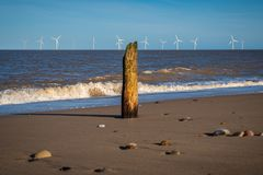 North sea coast in Caister-on-Sea, Norfolk, England, UK. With a wave breaker at the beach and wind turbines in the background stock photography