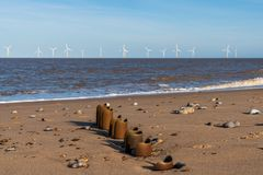 North sea coast in Caister-on-Sea, Norfolk, England, UK. With a wave breaker at the beach and wind turbines in the background royalty free stock images