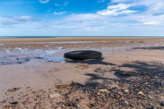North Sea coast in Cambois, England, UK. North Sea coast in Cambois, Northumberland, England, UK - and old tyre on the beach with wind turbines in the background royalty free stock photography